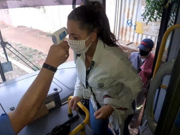 Motorista de ônibus aferindo temperatura de passageiros